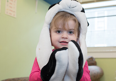 Child wearing a black and white panda hat and mittens