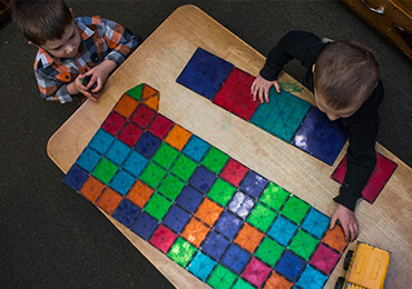 Two children playing with multi-colored magnetic tiles