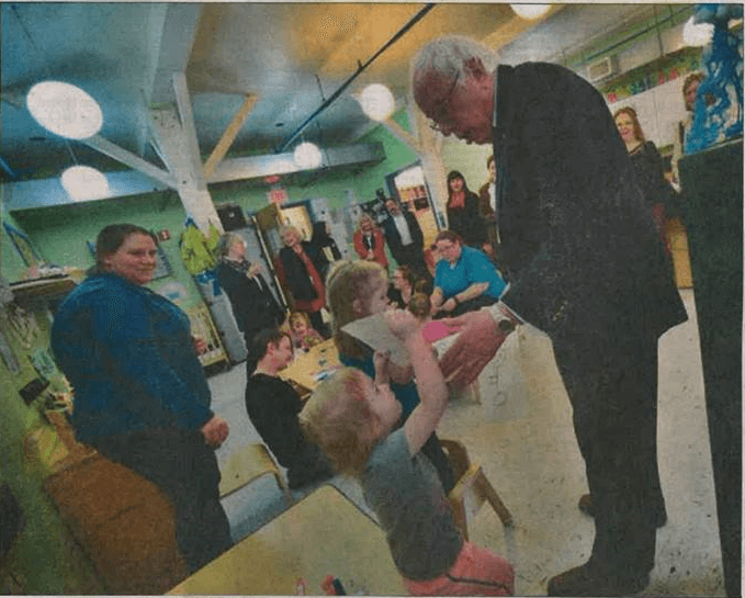 Harlequinn, a little girl enrolled at EES, joyfully shows Bernie Sanders her artwork in this photo from the Bennington Banner