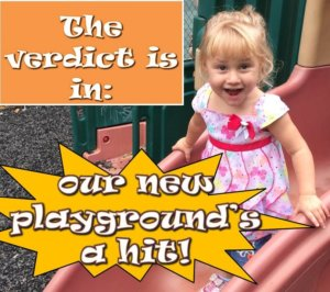 "A little girl smiles excitedly at the camera while standing on top of a slide in our new playground. The text around her reads: ""the verdict is in: our new playground's a hit!"""