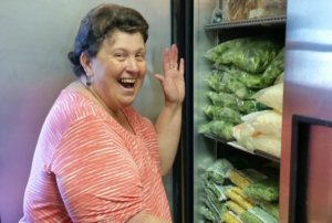 A photo of Pat smiling next to a refrigerator stocked with food.