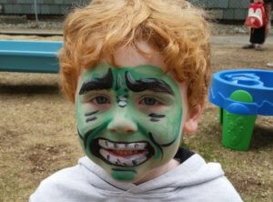A little boy with his face painted to look like the Incredible Hulk smiles at the camera