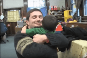 A screen capture from the Engaging Fathers video of a father embracing a child.
