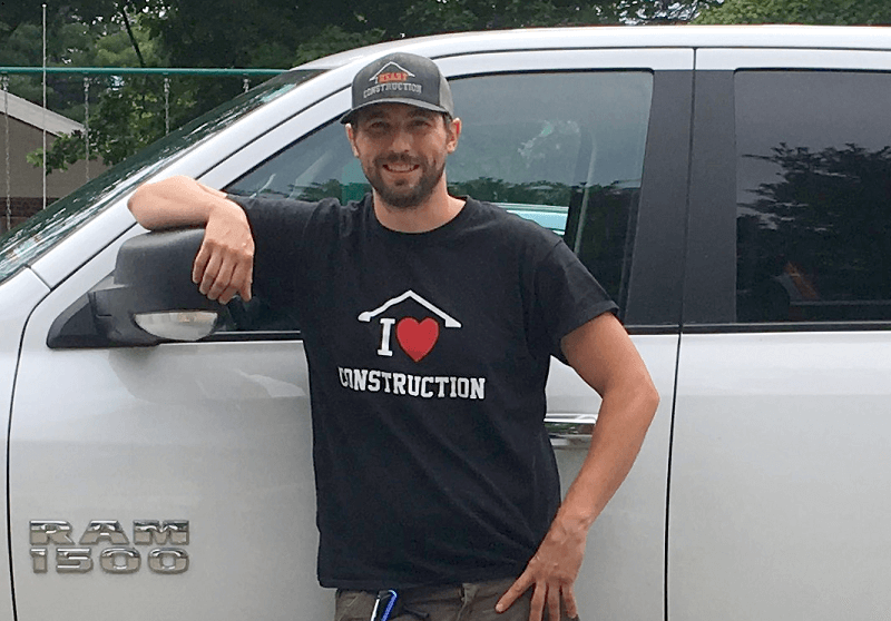 "Joe stands by his truck wearing his ""I love construction"" shirt and cap."