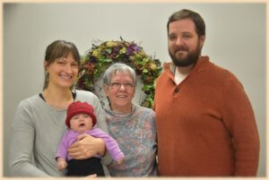 Jean poses in the center of this photo with a family and their baby in a berry hat!