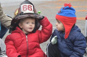 A little boy in a red coat smiles as he tries on a real firefighter's hat