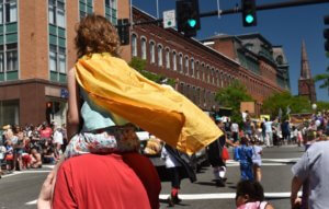View from behind of a little girl perched atop a man's shoulders in the parade. The little girl wears a yellow cape that is fluttering in the wind.