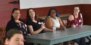 A panel of parents seated at a table laughing together at the World Cafe Event