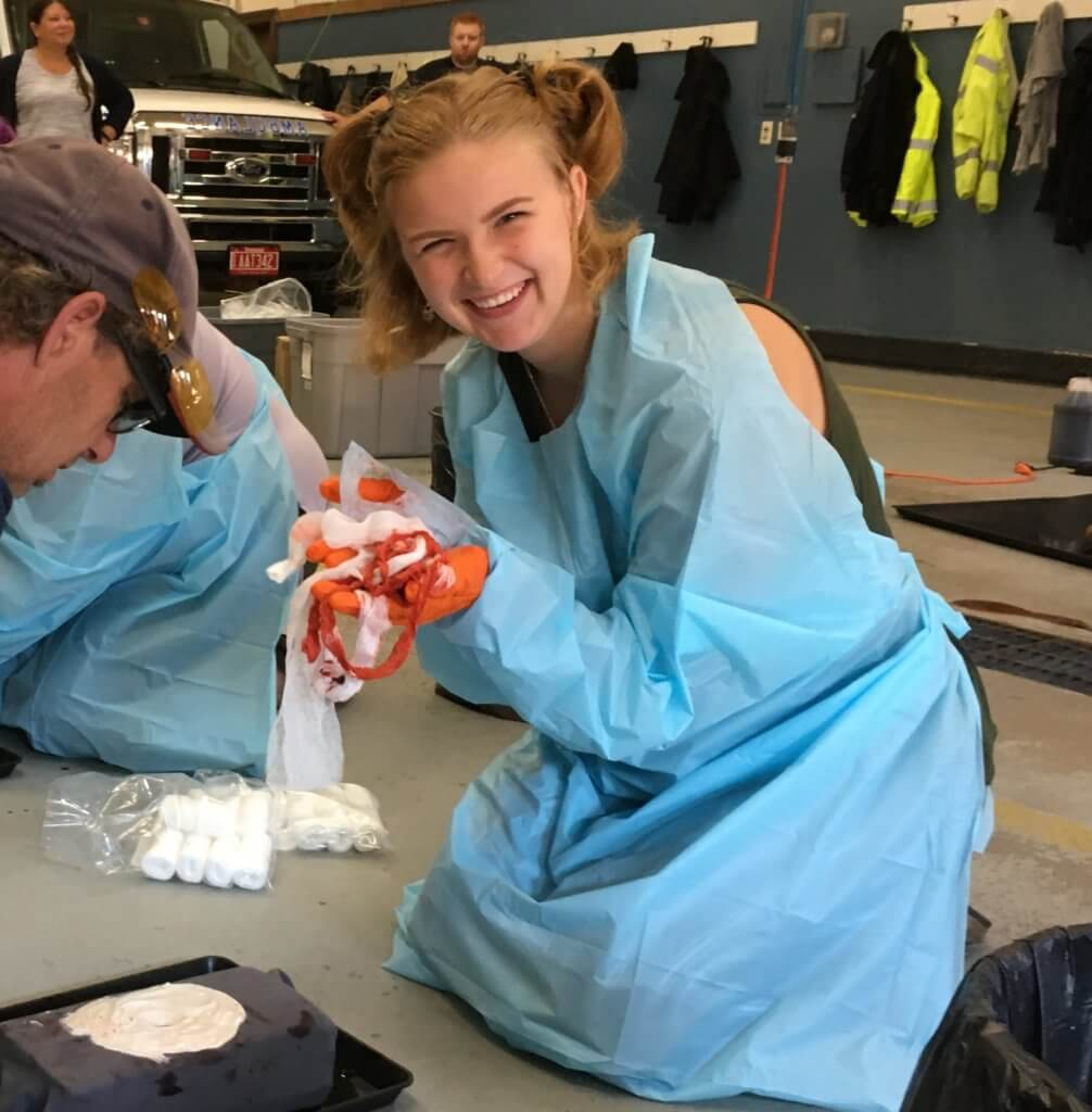 A young woman smiles as she holds bundle of gauze used in a bleeding emergency simulation