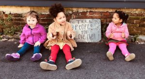 "Children sitting by sign that reads ""Tell people you love them"""