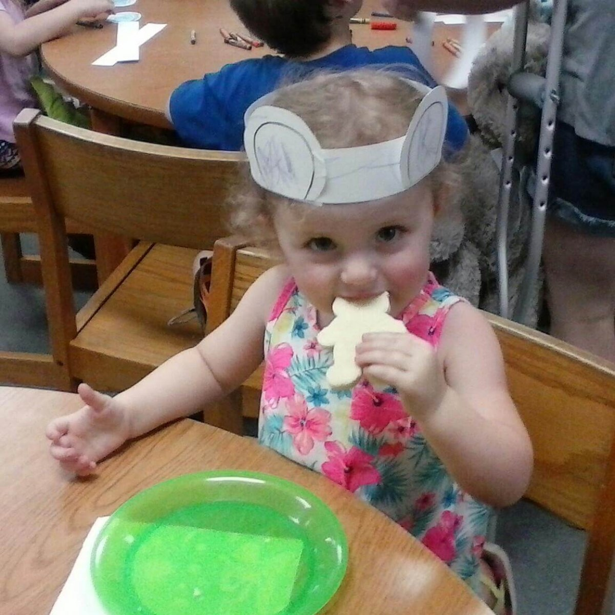 A little girl wearing a flowered dress and a paper headband with teddy bear ears takes a bite out of a cookie at one of the Teddy Bear Teas.