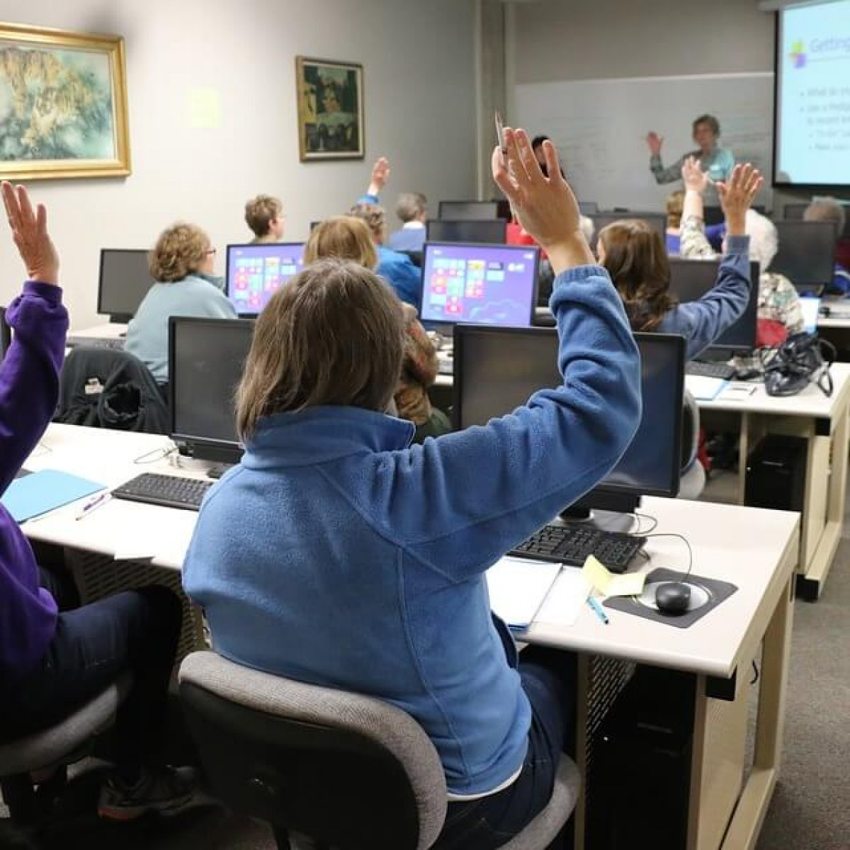 A photo of adult students seated at desks raising their hands