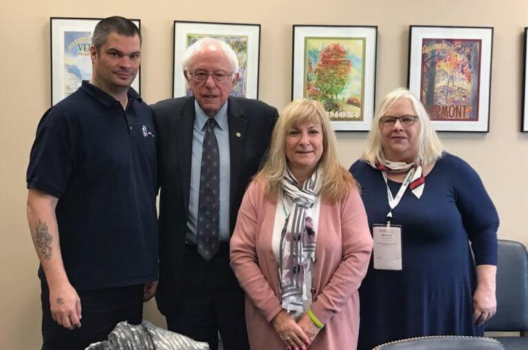 From left to right: Jay Isakson, Bernie Sanders, Deb Gass, and Marianne Miller stand together for a photo.