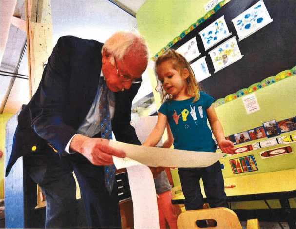 Elizabeth Howe, a little girl at EES, points to her artwork as Bernie Sanders bends down to examine it.