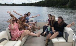 Staff strike a pose as they ride the pontoon boat across Lake Morey