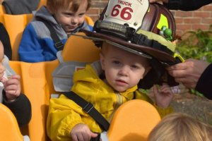 Little boy looks at the camera as he tries on a real firefighter's hat